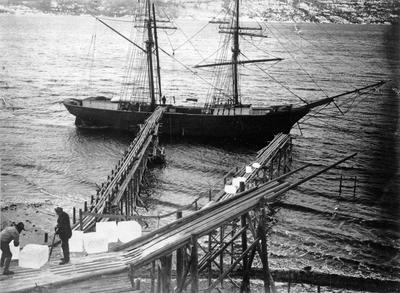 Svart-hvitt foto av fartøy med to master, i forgrunnen to mann som laster is ombord.. Foto/Photo