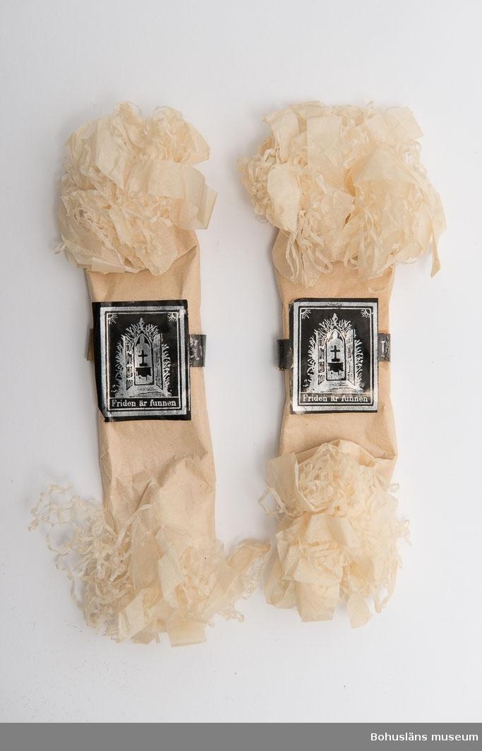 """Tillhört givarens föräldrar handlaren Gustaf och Annie Karlsson, Lysekil, som fått dem vid begravning. Vitt silkespapper, fransat och krusat i ändarna. Svart och silver bild med nygotisk dekor av port med kors innanför samt text: """"Friden är funnen"""" samt ett pappersband runt karamellerna med text i silver mot svart botten: """"Gud är kärleken"""" respektive """"Ditt minne skall hos oss fortlefva"""". Se bilaga."""