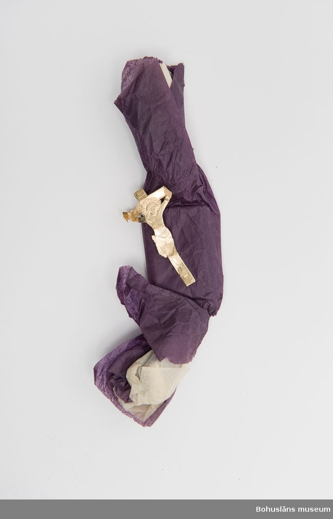 Tillhört givarens föräldrar handlaren Gustaf och Annie Karlsson, Lysekil, som fått den vid begravning. Vitt och lila silkespapper virat kring karamell. Pappersbild i guld. Se bilaga.