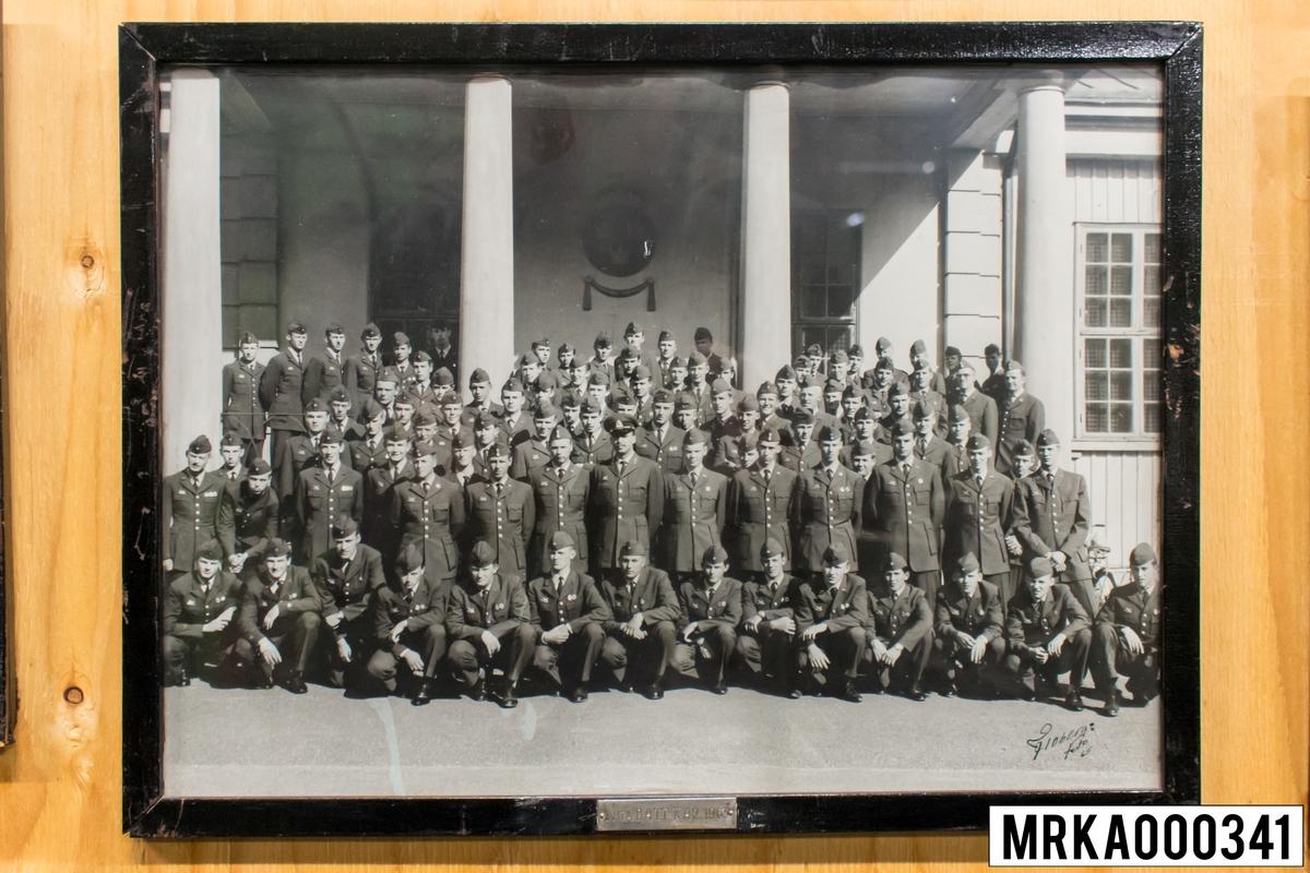 Fotografi taget på befäl och soldater som genomfört grundläggande soldatutbildning på 1:a Batteriet KA 2. Fotografiet taget utanför gymnastiksalen Gräsvik KA 2. Flobergs Foto 1963.