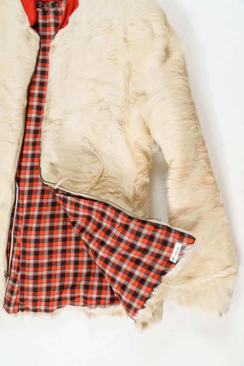 Jakke i kvitt geiteskinn. Glidelås i opninga og i dei to lommene på framstykket. Kort ståkrage i raudt tøy. (syntetisk?) Fóra med raud- ruta bomulls tøy. Løpegang i livet med snor.