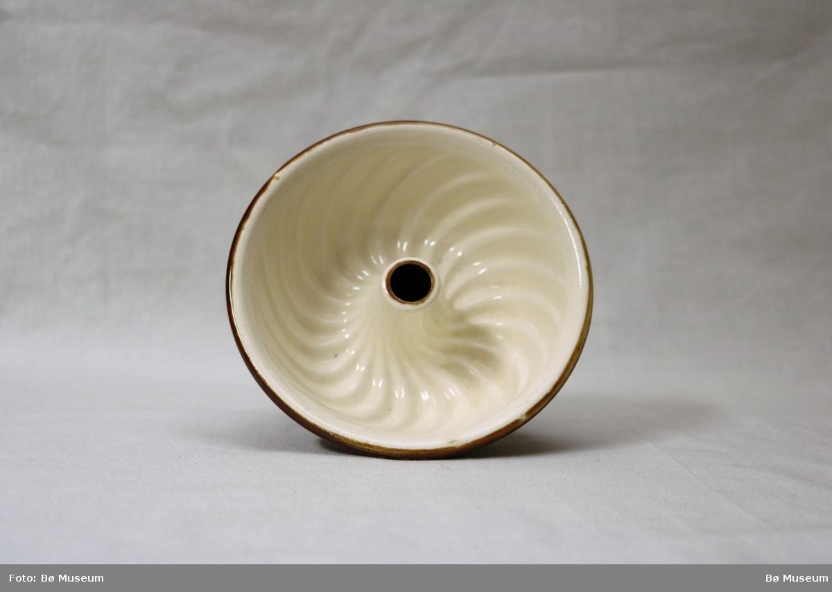 Rund form med hol/sylinder i midten, låg fotring og opphøgd viftemønster innvendig.