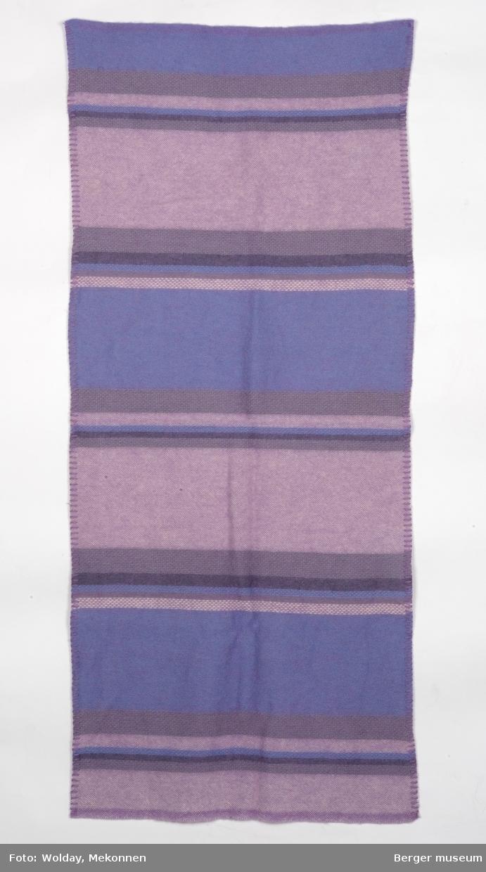 En pleddprøve i stripemønster. Prøven har jarekanter på kortsidene, de to langsidene har sydde kanter. Mønsteret karakterisereres av tverrgående felt og striper i forskjellge farger. Fargeholdningen er duse lilla toner.