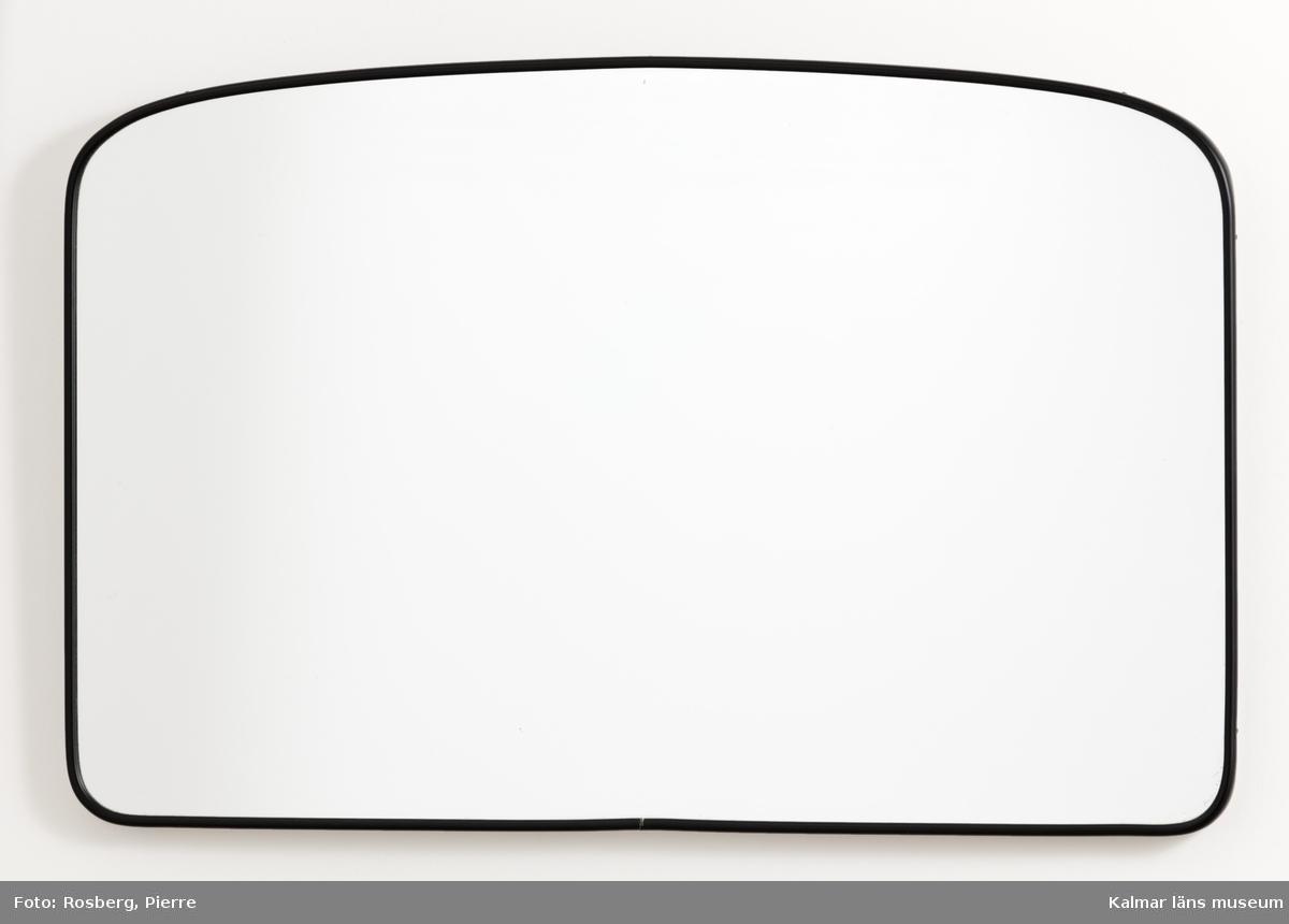 KLM 28668:155 Spegel, väggspegel av badrumstyp. Rektangulär i liggande format med rundade hörn och svängd överkant. Smal svart backelitkant. Blindram av vitmålat trä på baksidan. Glaset skyddat på baksidan med tämligen tunt papper innanför träramen. En mycket liten beläggningsskada nära nederkanten.