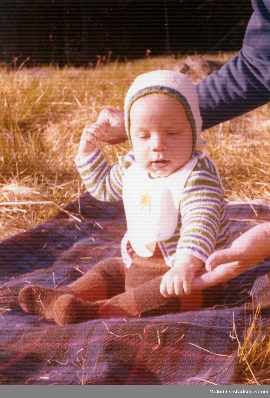 Filten ligger på en äng med halvhögt gräs år 1974. Man ser händerna av en vuxen person som håller i Martin (född 1974-01-12) som stöd. Babyn är givarens storebror.