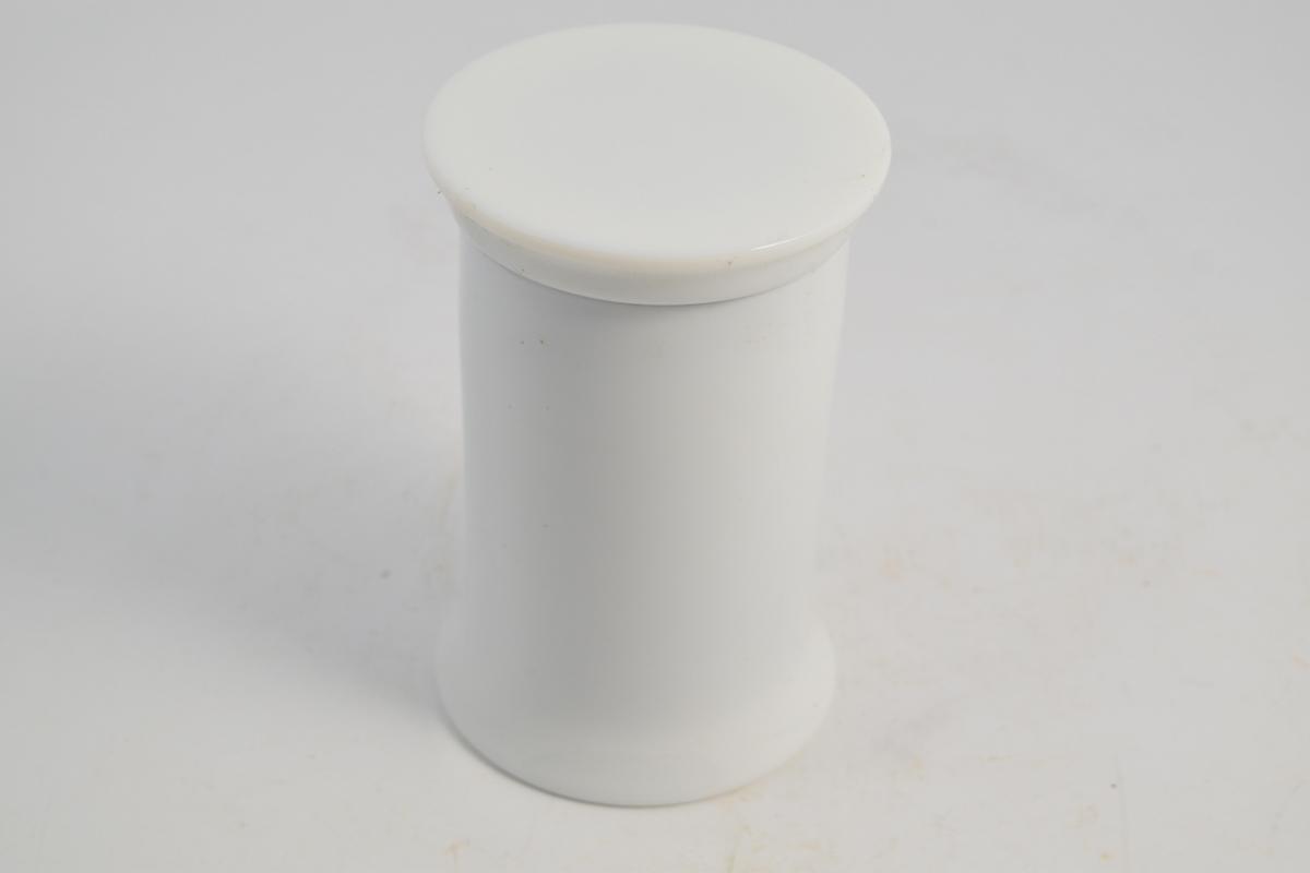 Sylinderformet porselenskrukke med porselenslokk. Hvit med rød skrift i rød ring. Superoxyd mangan er det samme som manganperoxyd. Krukken ble brukt til oppbevaring av manganperoxyd pulver.