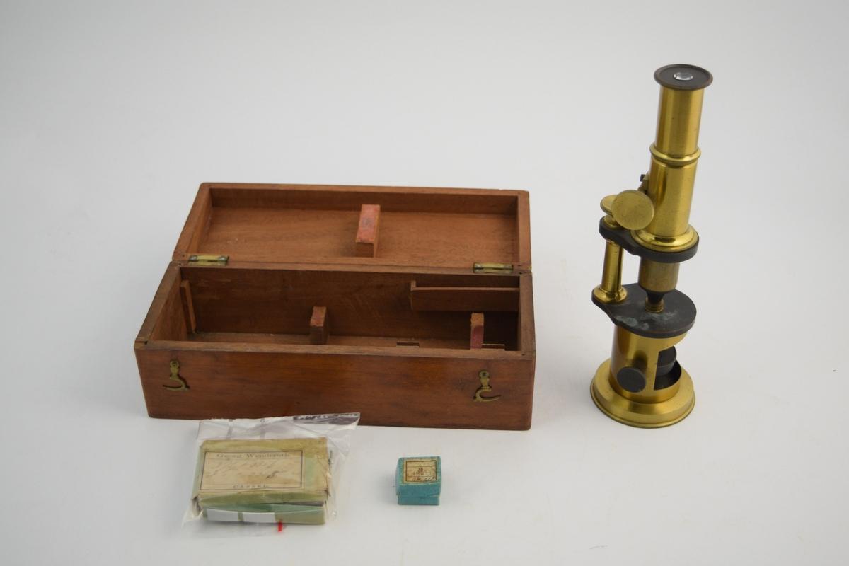 Mikroskop lagt i trekasse. Trekassen er brun, lakkert. Mikroskopet av metall, hovedsakelig messing. Glassplater lagt i to esker. Mikroskopet ble brukt på løveapoteket til identifisering av medisinplanter.