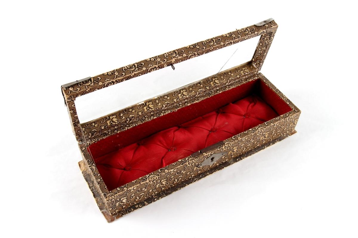 Avlangt smykkeskrin med hengsler og lokk. Lås og hjørnebeslag i metall. Lokket har et glassvindu. Foret med tekstil. Brukt til oppbevaring av små smykkegjenstander og en liten nøkkel.