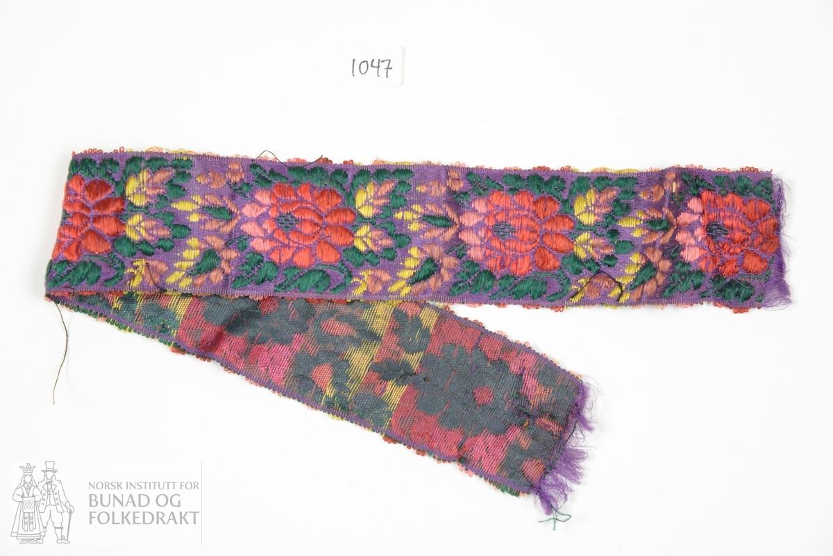 Band, satengbotn. Silkeband med blomstermønster i fleire fargar.