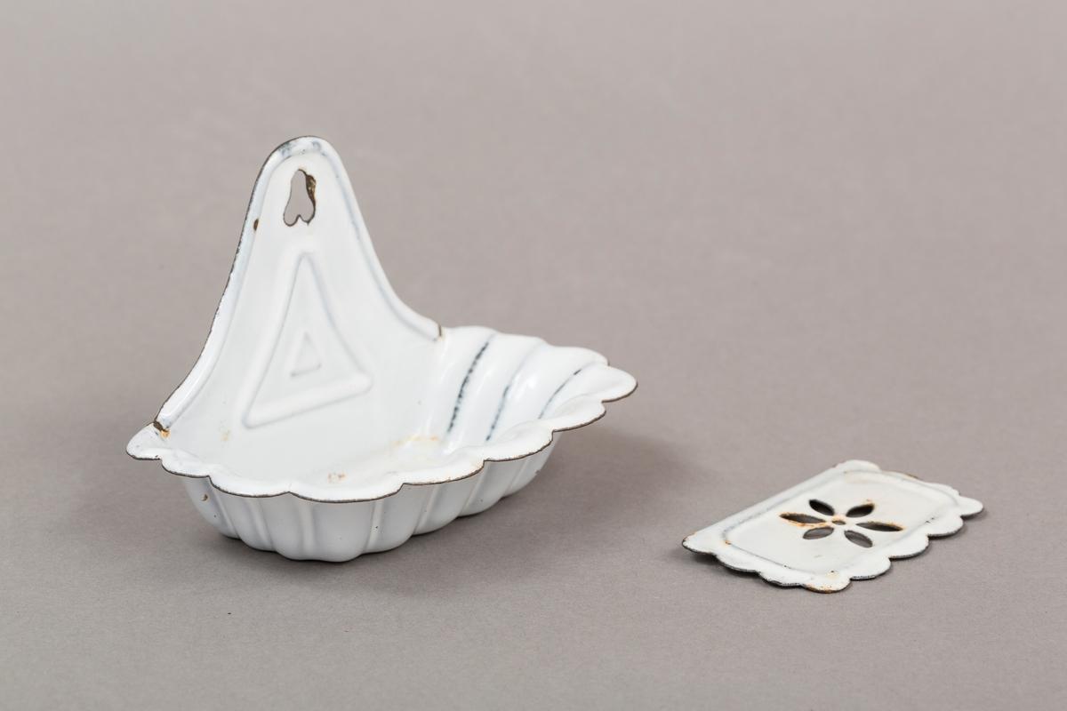 Holder til såpe. Skjellmønster i form. Løs plate i bunn. med utskåret blomstdekor. I metall, emaljert. Hvit.