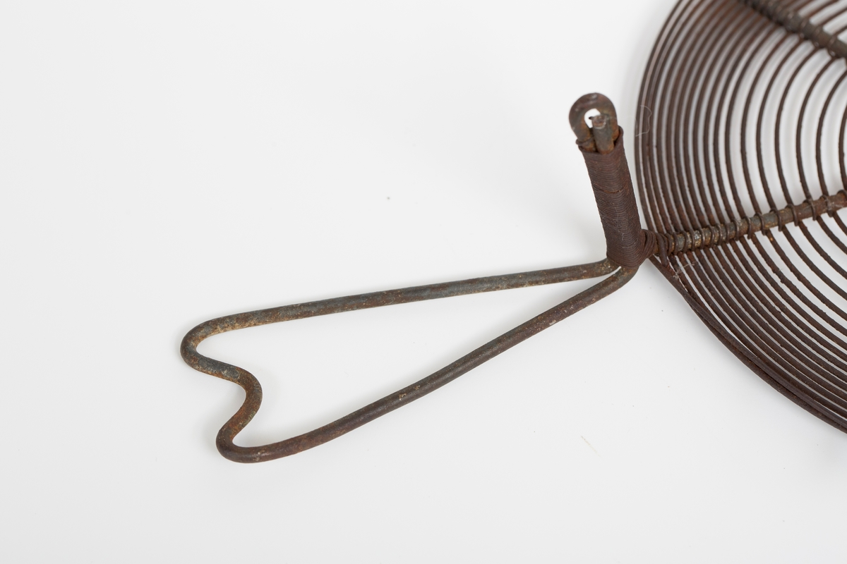 Rund gryteunderlag med håndtak og seks bein laget av ståltråd.