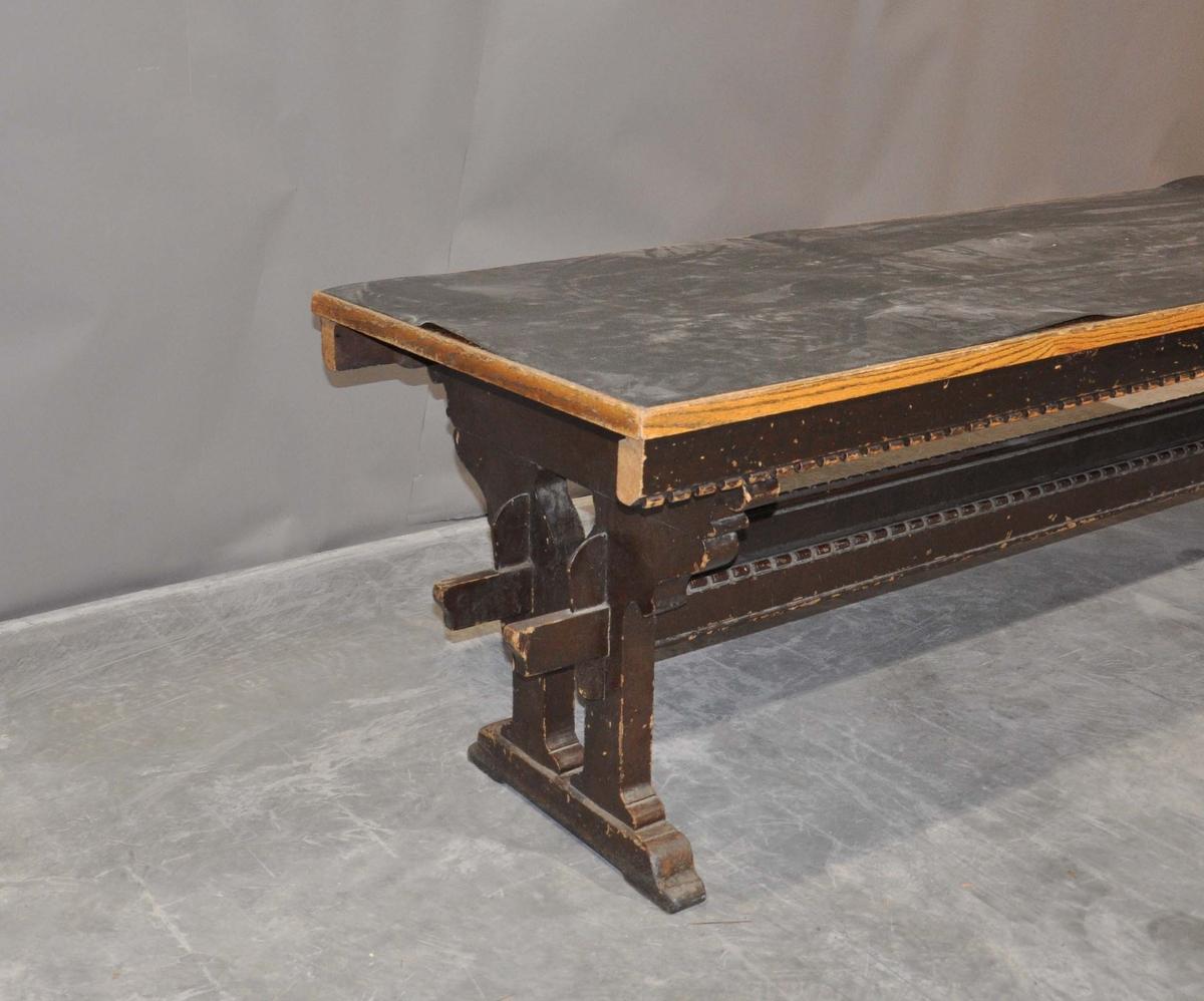 Brunbeiset arbeidsbord med pålimt gulvbelegg.
