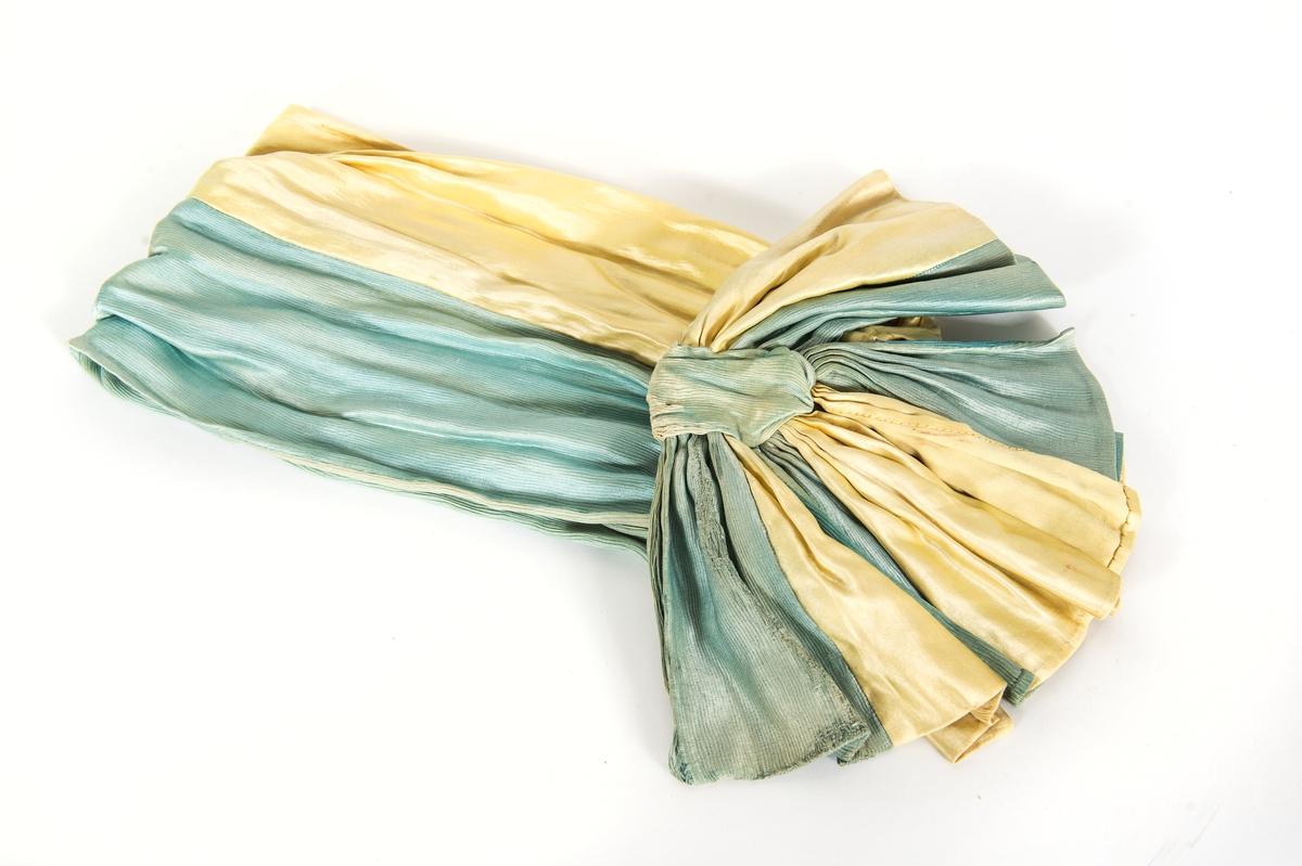 Skärp gult och blått siden, med stor rosett, hålles med hyskor och hakar.