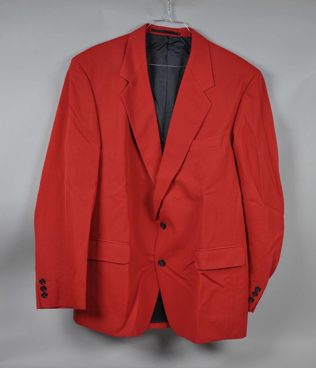 Rød ullgabardin-jakke , toknappet med en skrå brystlomme og to lommer med klaff. Tre innerlommer. Mørkeblått for i viscose.