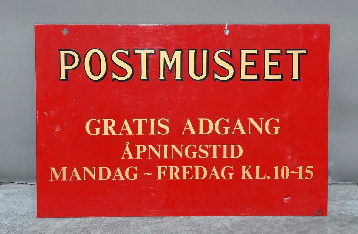 Rødt opplysningsskilt med gullfarget skrift.