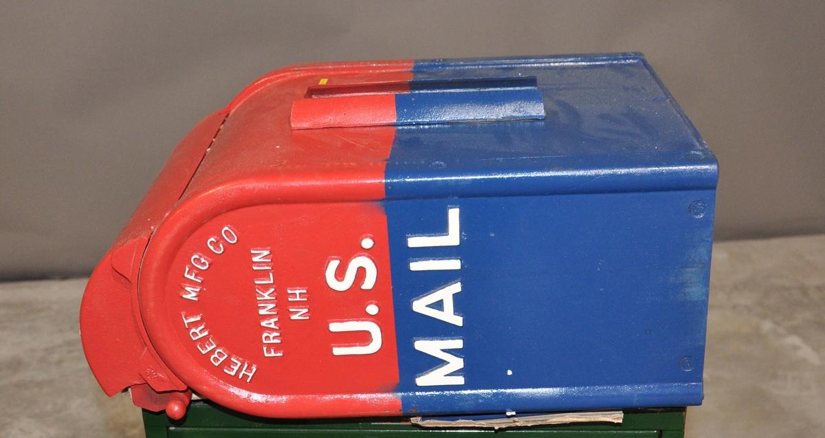 Rød, hvit og blå postkasse av jern med avrundet topp.