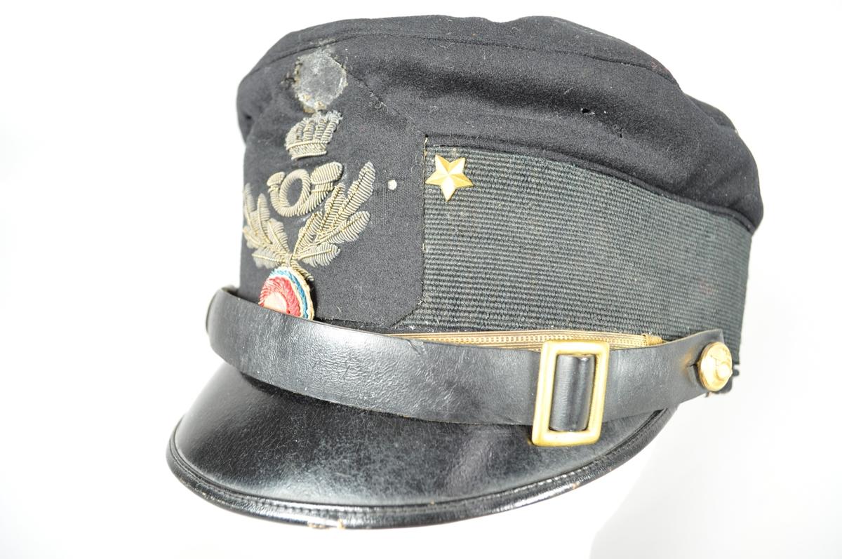 Uniformslue med skygge for postmester.  Påsatt merke med posthorn og ekeløv, gulltråd. To stjerner og trokolor.