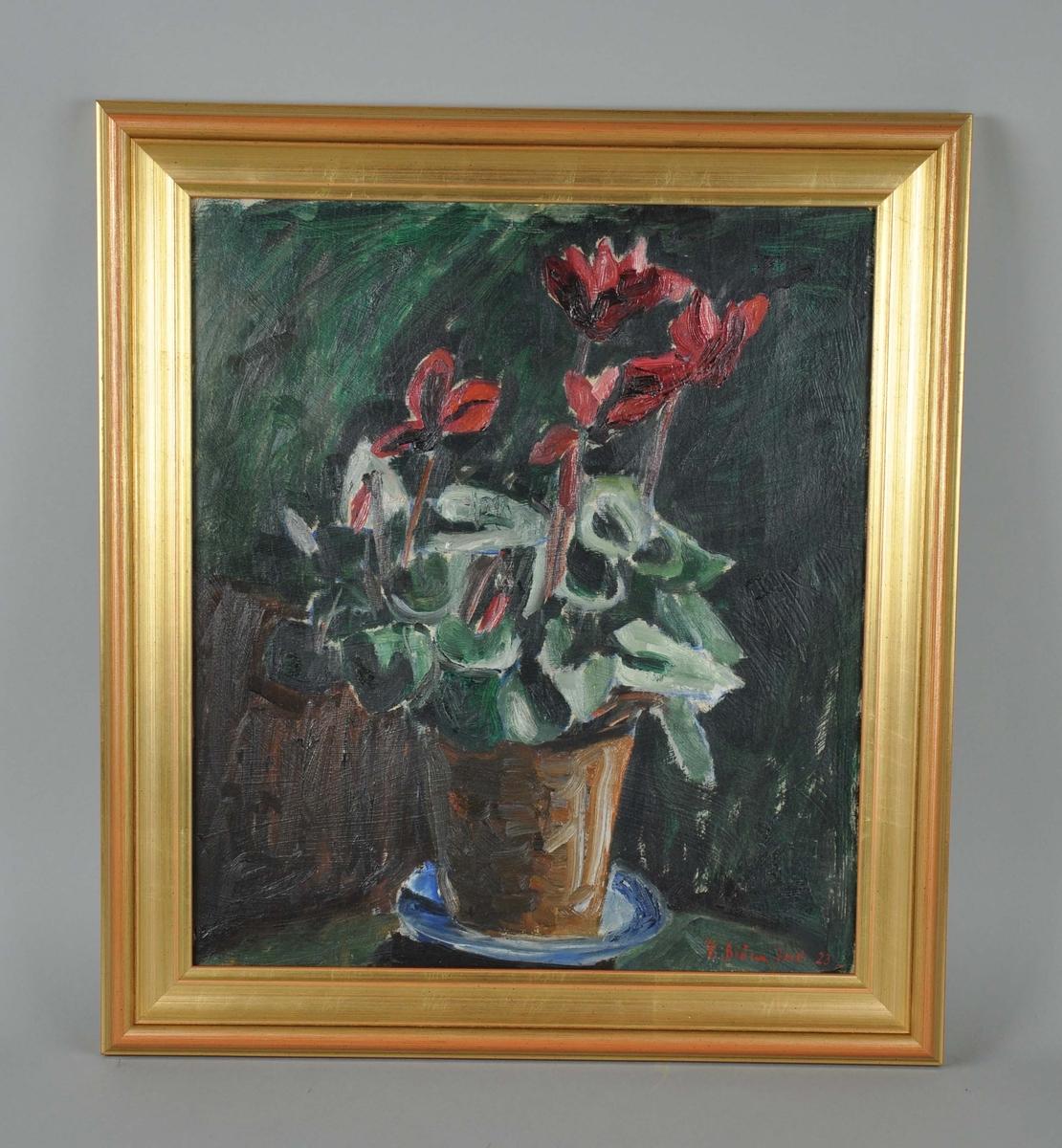 Maleri i stående format, med motiv av røde blomster i krukke på et bord. Rammen er av profilert tre med gullmaling på overflaten, sannsynligvis er rammen original.