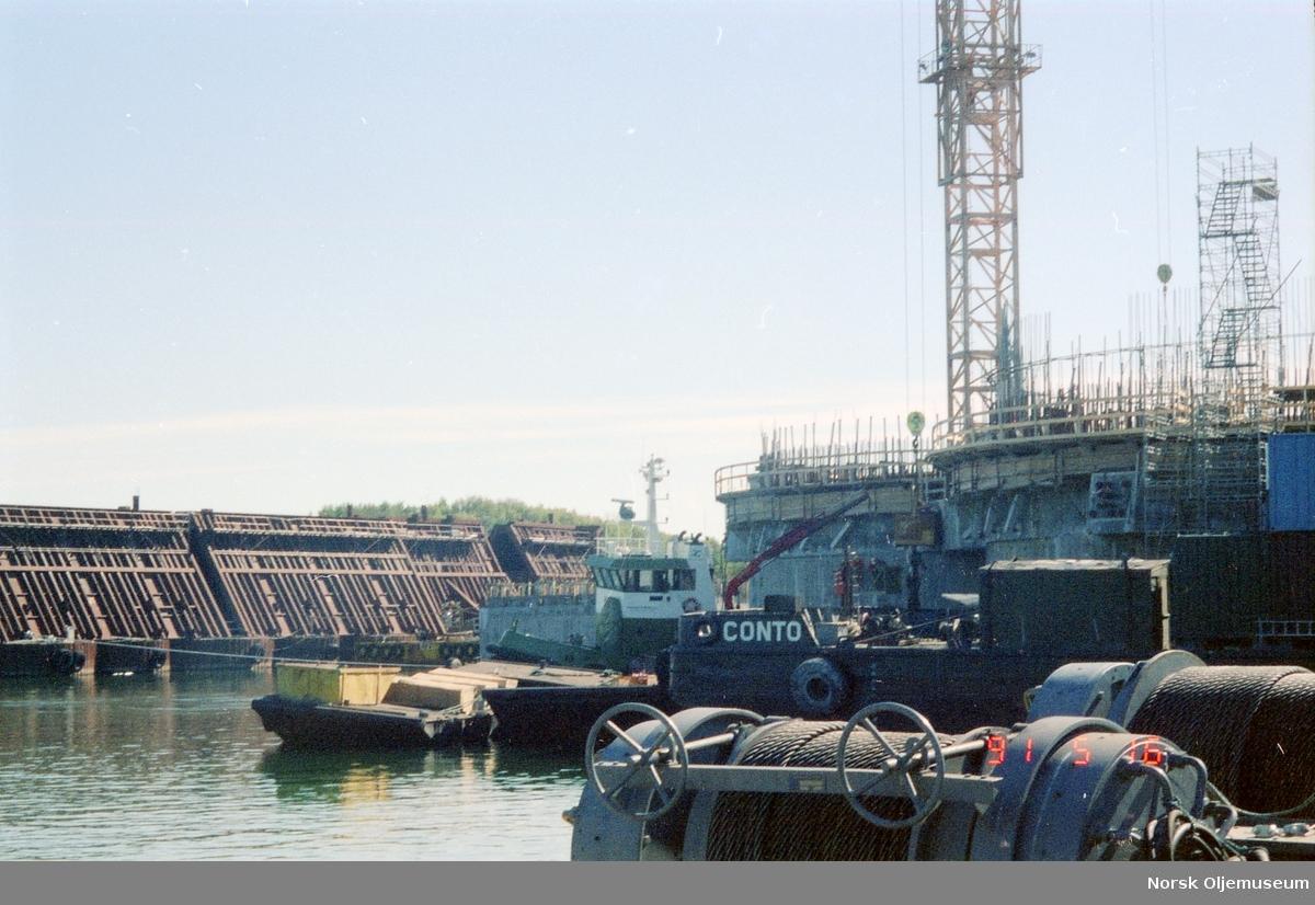 Anleggsområdet med dokkene til Norwegian Contractors. Lektere og slepebåter samt forskalingsformer i bildet.