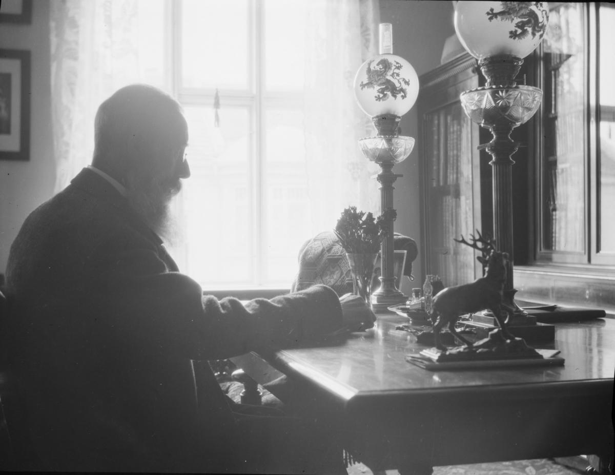 Eldre mann ved sitt skrivebord