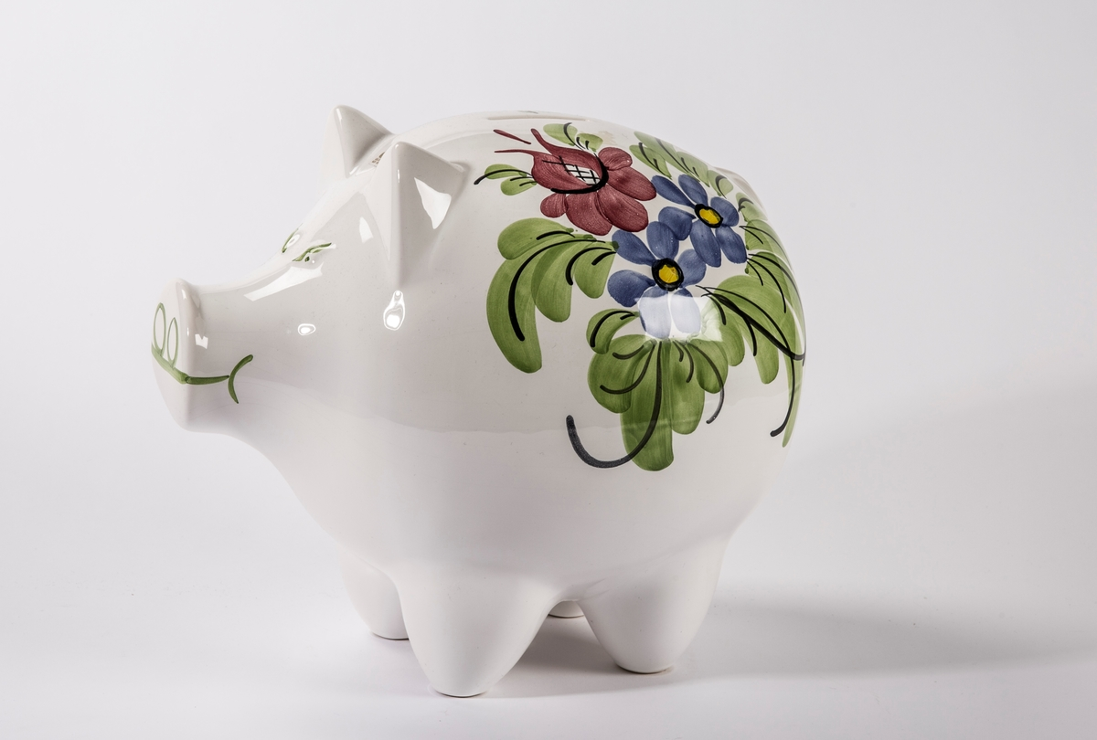 Sparebøsse formet som en gris med påmalte blomster på ryggen.