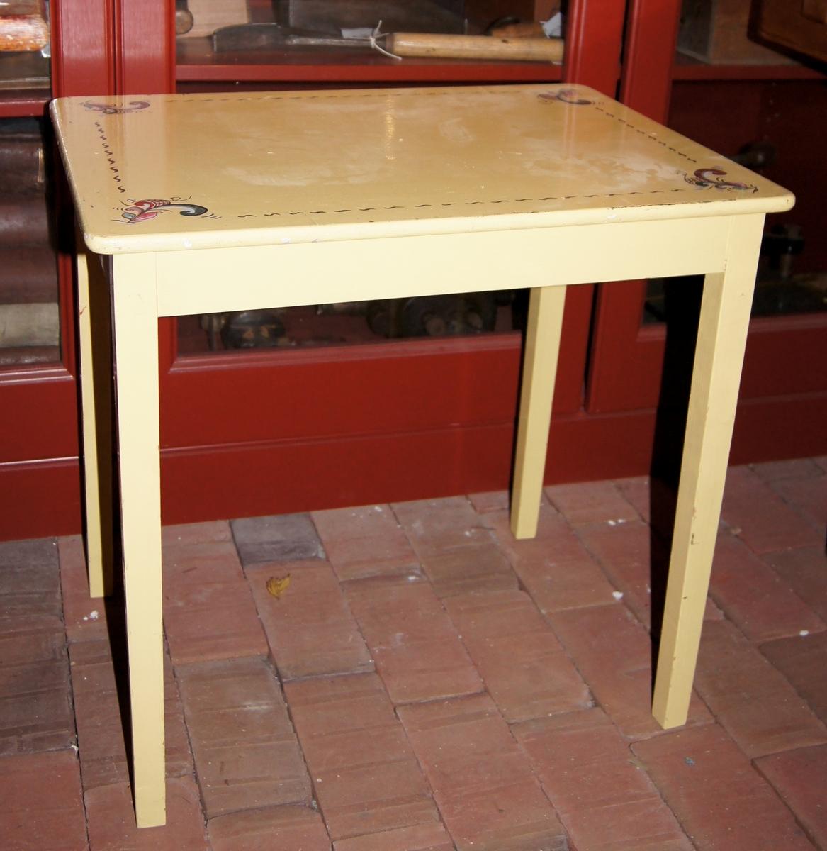 Barnemøbler i tre. Bord, stol og kommode med tre skuffer. Møblene er gule og har påmalt blomsterdekor.