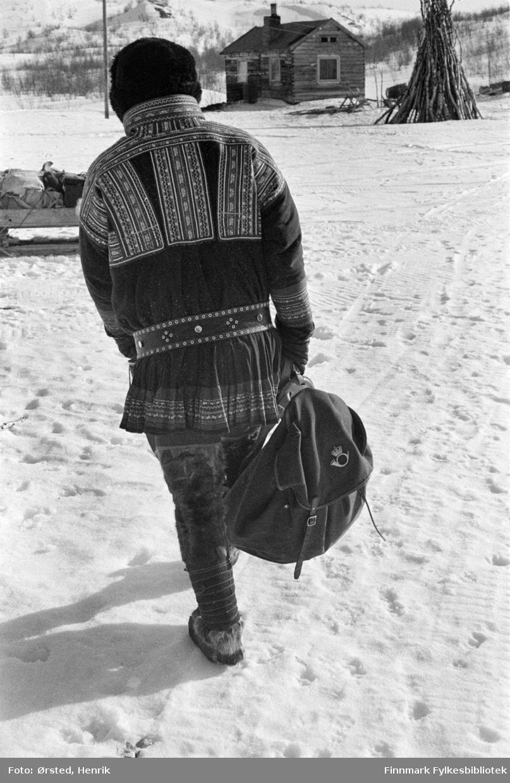 """Postfører Mathis Mathisen Buljo, bedre kjent som """"Post-Mathis"""" i samiske kretser, bærer postsekken med post til kunder i en siida han besøker på postruta.   Fotograf Henrik Ørsteds bilder er tatt langs den 30 mil lange postruta som strakk seg fra Mieronjavre poståpneri til Náhpolsáiva, videre til Bavtajohka, innover til øvre Anárjohka nasjonalpark som grenser til Finland – og ruta dekket nærmere 30 reindriftsenheter. Ørsted fulgte «Post-Mathis», Mathis Mathisen Buljo som dekket et imponerende område med omtrent 30.000 dyr og reingjetere som stadig var ute i terrenget og i forflytning. Dette var landets lengste postrute og postlevering under krevende vær- og føreforhold var beregnet til 2 dager. Bildene gir et unikt innblikk i samisk reindriftskultur på 1970-tallet. Fotograf Henrik Ørsted har donert ca. 1800 negativer og lysbilder til Finnmark Fylkesbibliotek i 2010."""