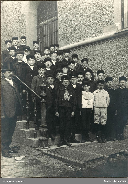 Avgångsklass med läraren Johan Vallin i hög hatt på trappan till folkskolan, Gustav Adolfs-skolan. Längst  upp (6:e fr höger) står Sam Andersson (född 1894-01-19).