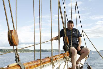 """Mann sitter i masta på skonnerten """"Svanen"""", land i bakgrunnen, klar himmel med litt skyer.. Foto/Photo"""