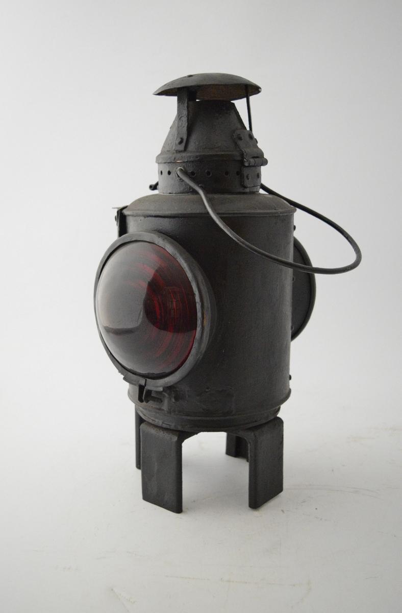 Parafinlampe. Sylindrisk hovedform med ett rødt og ett hvitt glass (buede, med optisk linse: fresnel) på motstående sider. En luke kan åpnes mellom glassene for å tenne lampen. Fire rektangulære ben nederst, avrundet hank øverst. Lampehatten er trolig satt på i ettertid og er ikke original. Brukt som sluttsignal ved jernbanetransport - hang på siste vogn i toget. Lyste rødt bakover og hvitt fremover.