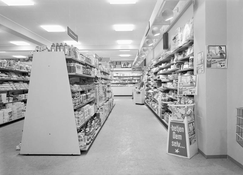"""Skiltet med """"Betjen Dem selv..."""" forteller at kundene måtte venne seg til nye måter å handle inn på i butikken.  Bildet stammer fra Asbjørn Olaussens kolonial i Strømmen 1965. Foto: Asbjørn Kåre Gundersen, MiA"""