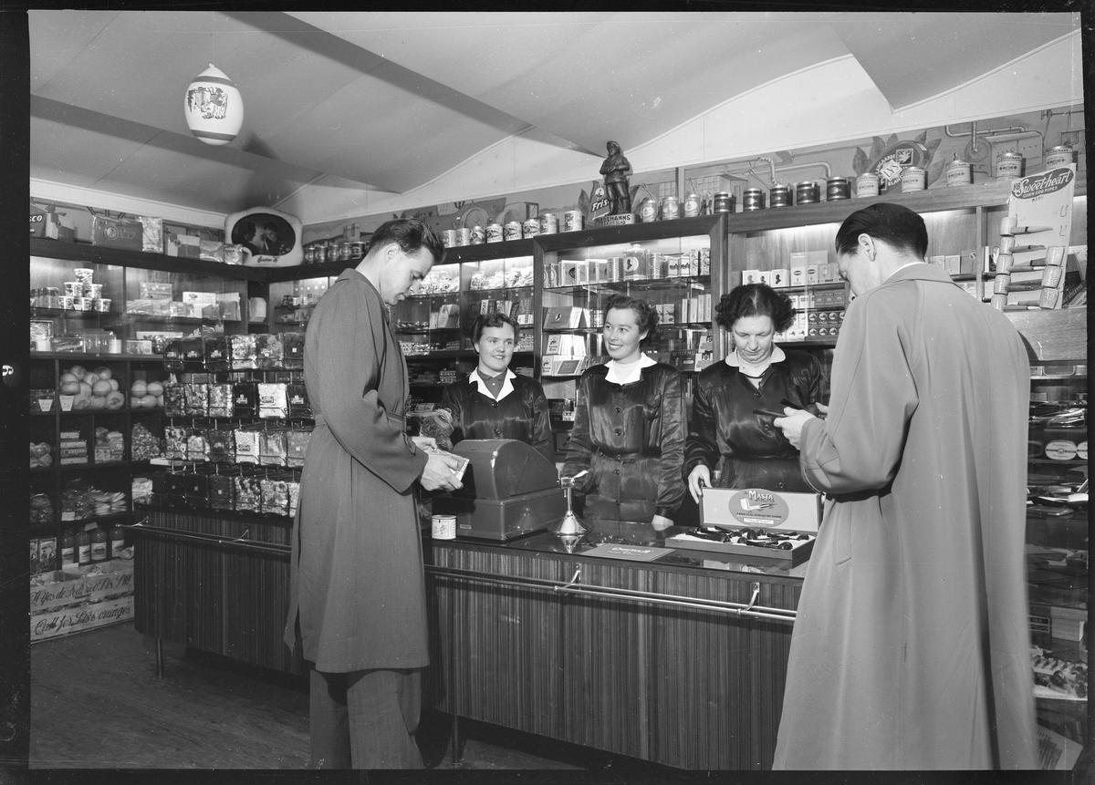 Tobakksinnkjp_over_disk._Butikkbetjening_og_kunder_i_Christian_thomsens_tobakksforretning_pa_Strmmen_1955_-_Foto_Asbjrn_Kare_Gundersen_-_MiA.jpg