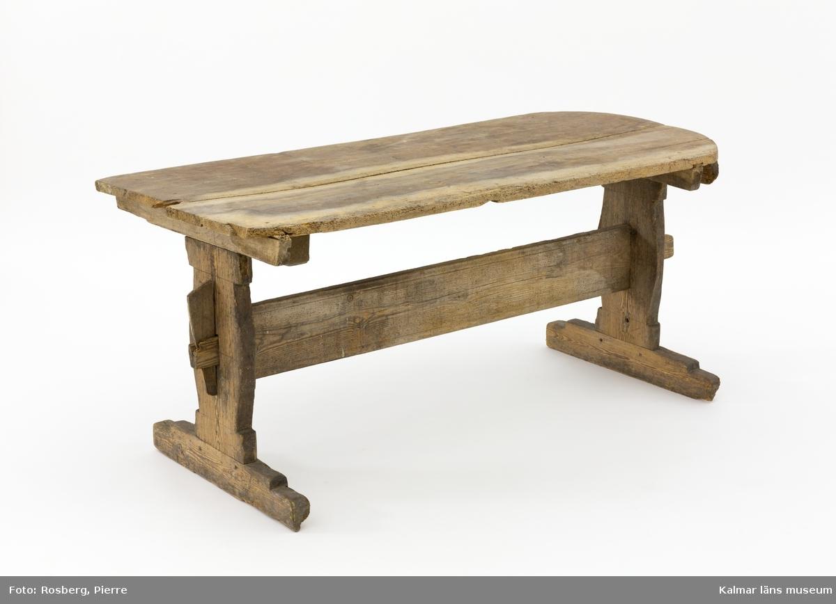 KLM 10287. Bord, långbord. Av furu. Avlångt bord med breda ben och en mittslå samt lös bordsskiva som är rundad i ena änden. Omålat. Väl använt. Bordsskivan är troligen återanvänd då den på undersidan är mycket nött med märken efter exempelvis användning av kniv.