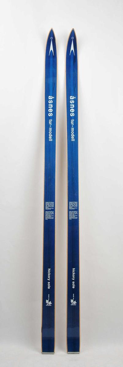 Langrennski for barn laga av tre. Blå overside med kvit skrift og emblem i skitupp. Metallbeslag på baktupp.