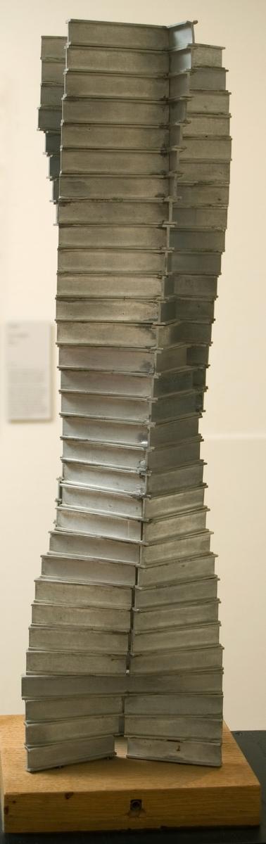 """Skulptur i aluminium. Arne Jones """"Mänsklig byggnad"""" 1960. Uppbyggd av prefabricerade I-balkar som staplats på varandra i två vridna, motställda positioner (31 st i höjd)."""