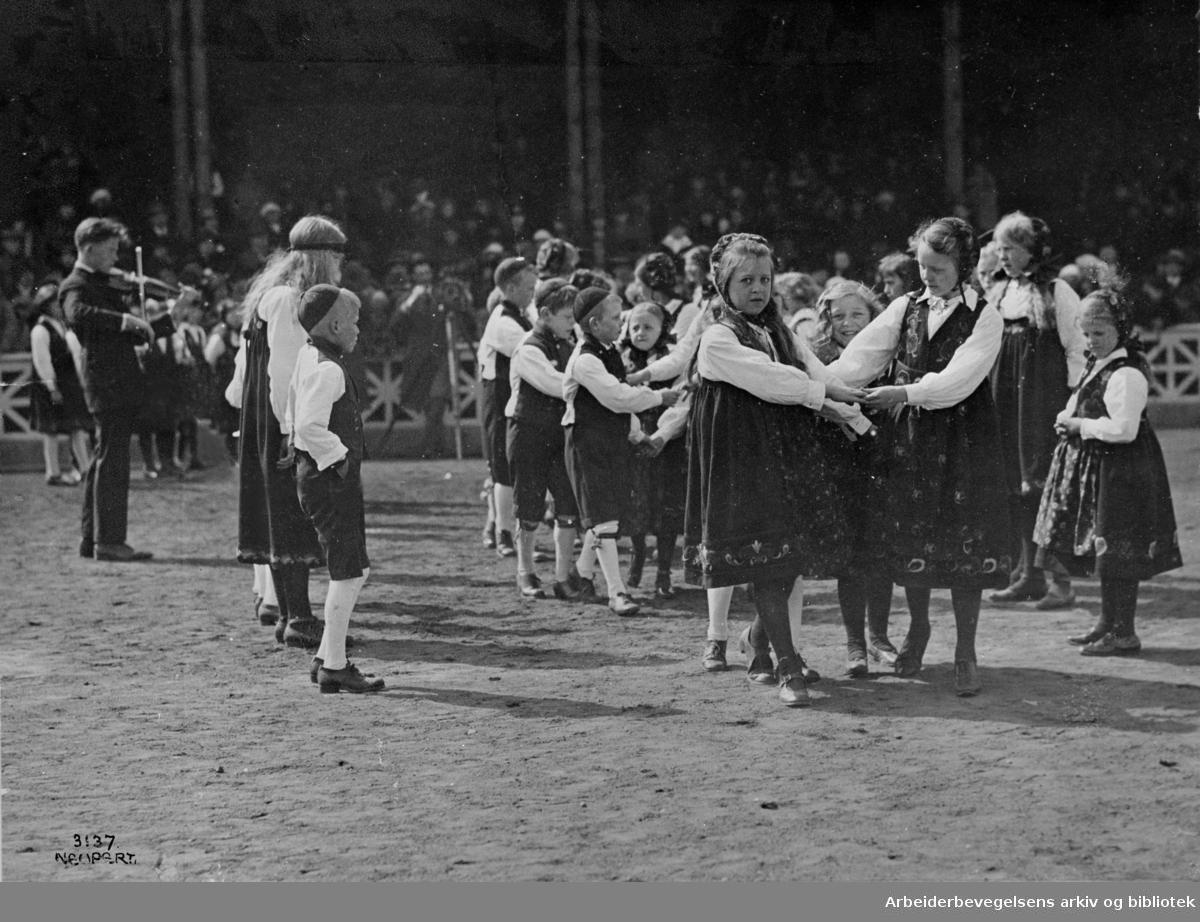 """1. mai 1925, fra barnestevnet på Bislett stadion. Leikarring fra et barnelag som opptrer, antakelig en folkedans fra Namdalen """"Seierstadhopsa""""."""
