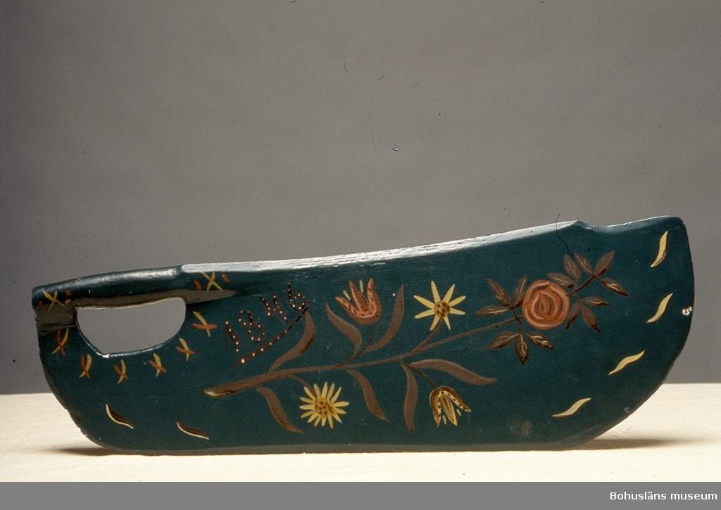 """Platt, avlångt redskap för att slå ut """"bosset"""" ur linet. Det har ett handtag baktill och är bredare framöver med en """"tå"""" allra längst fram. Sekundärt målat med mörkgrön färg i botten. På en av sidorna är en målning med en blomsterkvist bestående av bland andra två tulpaner och en ros ytterst samt årtalet """"1846"""". Även den sekundär. Färgen är avslagen på ett ställe och där skymtar en blå färg. Skäktkniven kan vara av äldre datum än målningens årtal. Kan vara en friargåva.  Ur handskrivna katalogen 1957-1958: Skäktkniv för linberedning L.: 49,8 cm. Största br.: 17,3 cm. Grönmålat trä. Mönster med blomrankor och """"1846"""". Hel.  Litt.; Fredlund, Jane, Stora boken om livet förr, ICA-förlaget, Västerås, 1981, s. 30-40."""