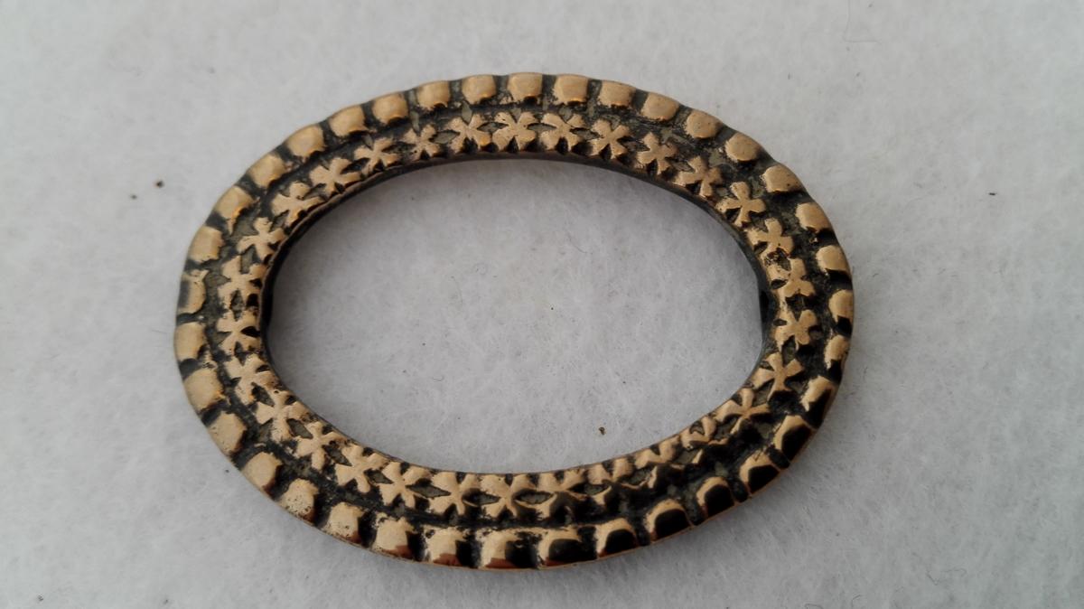 2 ovale knæspender av messing.  Den ene mangler tand.  Støpte orneringer.  No 397 - 400 kjøpt paa forskjellige steder i Indre - Sogn  1900 - 1906.