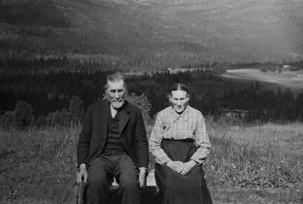 Eldre ektepar sitter på benk ute sommer