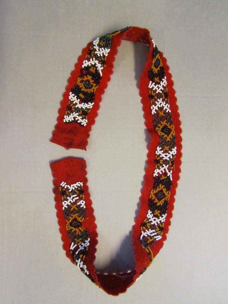 Beltet har born av rødt klede. Tredd band av småperler i forskjellige farger. Langsidene og eine enden har utstansa, taggekant med halvsirkler  ca 1 cm i diameter. Manglar spenne.