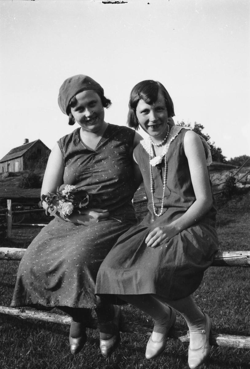 1b47533e1a35 Två finklädda flickor sitter på ett staket, den ena med en liten blombukett  och basker