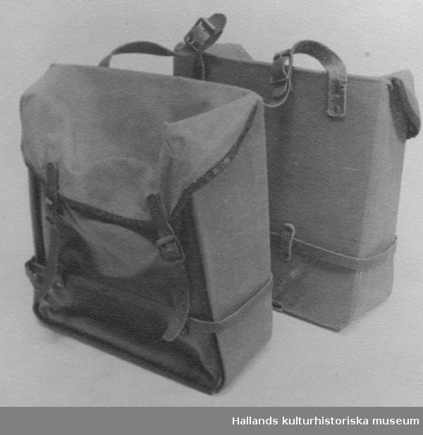 Ett par cykelväskor av kraftigt grått tuskaftat bomullstyg över en pappstomme. Band och spännen av läder. Rektangulär. Styva sidor, botten och rygg. Mjuk framsida och lock. De två väskorna hopsatta med två läderremmar.