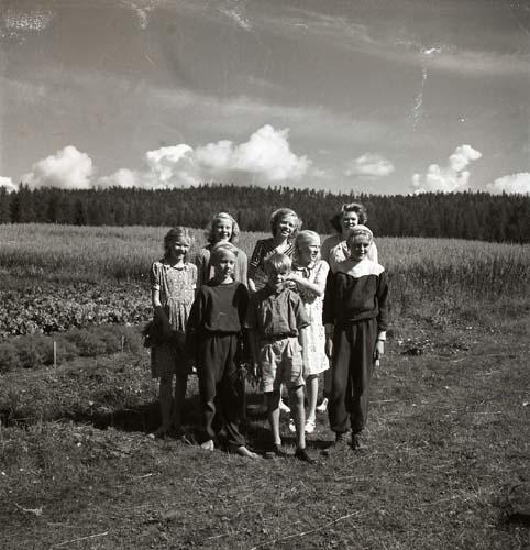 Veckebobarnen, Unga Odlare i Ovanåker, 1950. Några barn har ställt upp sig för en gruppfotografering på en åker.