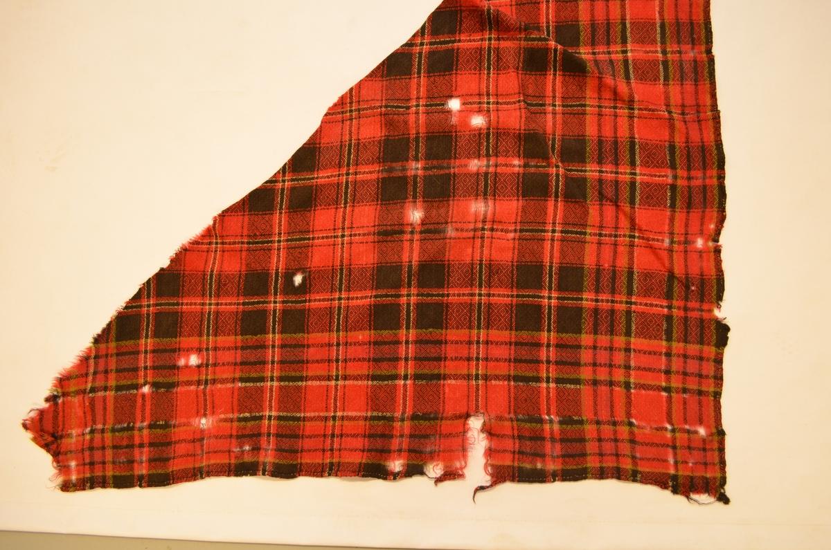 Sjal, trekanta ruta sjal vove i ringvend i sauesvart, raudt, grønt, og kvitt ullgarn. Falda langs kantane. Holete og fillete.