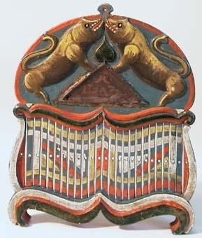Bandsked av trä. Skeden har bågformigt överstycke med snidad dekoration i relief på båda sidor, av bland annat två vildsvin. På ena sidan är de stående på bakbenen med huvudena mot varandra på ett triangelformat stycke. Skeden är målad i färgerna blått, rött, gult, vitt och brunt.Köpt av urmakare Bertil Linde, Jämtland.
