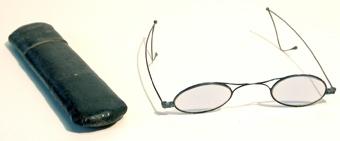 Glasögon för solförmörkelse. Ovala, svagt blåfärgade glas i tunna bågar av metalltråd.