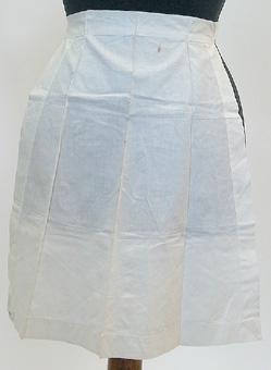 Serveringsförkläde sytt av vitt bomullstyg med korta knytband.