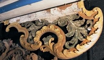 Flygelstycken i form av genombrutna, skulpterade ornament av trä, målade i guld och grönt.