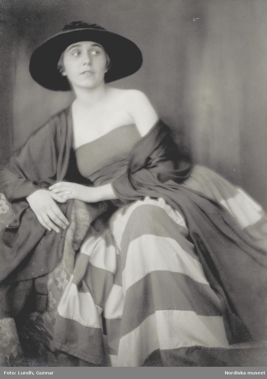 Porträtt av ung kvinna i bredbrättad hatt och randig klänning. Varuhuset Wertheims porträttateljé, Berlin.