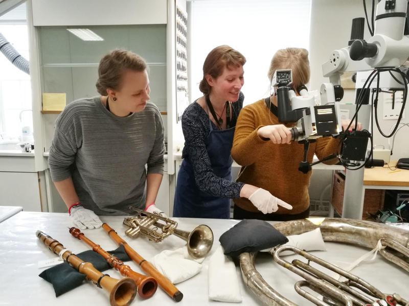 Vera de Bruyn-Ouboter (i midten) sammen med Monna Laari og Saara-Maija Pesonen. Her undersøker de metalloverflaten på ulike instrumenter for å se etter rust. Foto: Ringve Musikkmuseum